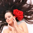Beautiful young woman with flower on her long hair. — Stock Photo