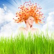 Beautiful woman with flowers on her long hair in fresh spring grass.  — Stock Photo