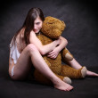 Young homeless girl is holding the teddy bear. Conceptual image - recession metaphor. — Lizenzfreies Foto
