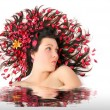 Bathing young woman with dried herbs on her long hair. — Stock Photo #33189749