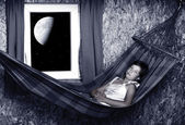 Resting young girl on a hammock in living room - nightshot — Stockfoto