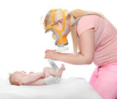 Mother in mask changing diaper newborn baby — Stock Photo