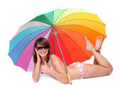Young woman in swimsuit resting under a beach umbrella. — Stock Photo