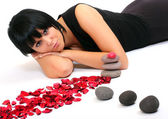 Woman with petals and stones — Stock Photo