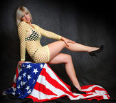 Pretty girl sitting on a american flag. Great for calendar — Stockfoto