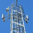 Telecommunications tower with a lot of different antenna against blue sky. — Stock Photo