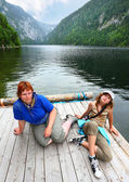 Tired hikers on mystic alpine lake — Stock Photo
