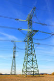 High voltage power tower and electrical lines against blue sky. — Stock Photo