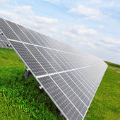 Solar energy panels on a green wheat field — Stock Photo