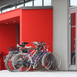 Several old bicycles at door to modern building — Stock Photo