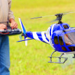 Stock Photo: Piloting Radio controlled helicopter (scale-model 1:24 scale) with remote control. Teleobjective shot with shallow DOF.
