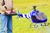Piloting Radio controlled helicopter (scale-model 1:24 scale) with remote control. Teleobjective shot with shallow DOF. — Stock Photo