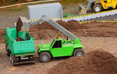 Green dumper and yellow excavator on a road building — Stock Photo
