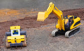 Yellow excavator on a road building — Stock Photo