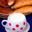 Milk in the cup and various fresh baked bread. — Stock Photo
