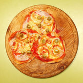 Tasty pizza on a wooden plate. — Stock Photo