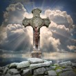 Ancient cross on the grave against sunset over a sea. — Stock Photo