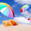 Beach with rainbow umbrellas flying — Stock Photo #33799703