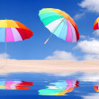 Beach with rainbow umbrellas flying — Stock Photo #33799979