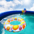 Inflatable pool with floating plastic toys. — Stock Photo