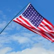 American flag waving against blue sky. — Stock Photo