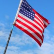 American flag waving against blue sky. — Stock Photo #33806577