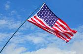 American flag waving against blue sky. — Stock Photo