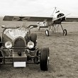 Historic racer and historic monoplane — Stock Photo