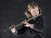 Young girl playing the flute — Stock Photo