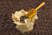 Sack of coffee beans and scoop with coffee beans background — Stock Photo