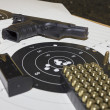 Gun and ammunition over bullseye score — Stock Photo #17010453