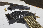 Gun and ammunition over bullseye score — Stock Photo