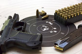 Gun and ammunition over bullseye score — Stock Photo