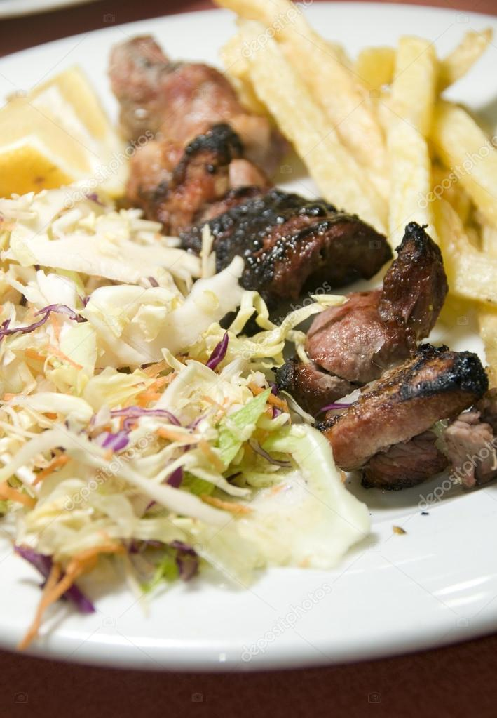 Pork and liver kabob shish kabab meal salad French fried potatoes as photographed in Tunis Tunisia — Stock Photo #12633492