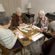 Senior woman at the game table - Stock Photo