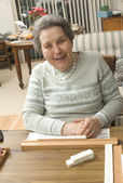 Senior woman at the game table — Stock Photo