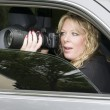 Female private investigator with camera - Stock Photo