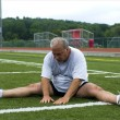 Middle age man stretching and exercising on sports field — Stock Photo #13073769
