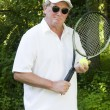 Middle age senior tennis player male demonstating stroke — Stock Photo #13074061