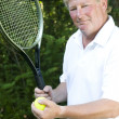 Middle age senior tennis player male demonstating stroke — Stock Photo #13074067