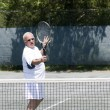Stock Photo: Middle age tennis player demonstrating the volley stroke on court