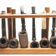 Stock Photo: Pipe collection in wood pipe rack