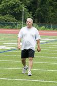 Uomo di mezza età esercitano sul campo sportivo — Foto Stock