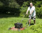 Homem cortar relva em casa suburbana — Fotografia Stock