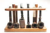 Pipe collection in wood pipe rack — Stock Photo