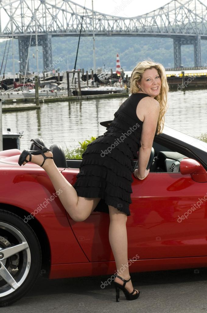 Sexy woman with red sports car by a yacht club on the  hudson river new york — Stock Photo #13071672