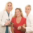 Постер, плакат: Two doctors nurses in medical scrubs clothes with patient