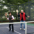 Man and woman playing paddle platform tennis - Stock Photo