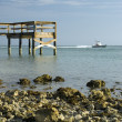 Pier rocky shoreline with boat — Stock Photo