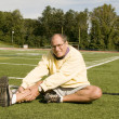 Middle age senior man exercising on sports field — Stock Photo